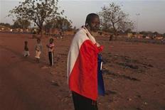 """Justo cuando sus líderes estaban definiendo una nueva estrategia de """"manos fuera"""" para África, Francia se ha visto empujada a la línea del frente de uno de los campos de batalla más arriesgados del continente en el profundo desierto de Mali. En la imagen, Yacouba Konate, de 56 años, se cubre con una bandera francea en señal de apoyo a la intervención militar francesa en la capital de Mali, Bamako, el 13 de enero de 2013. REUTERS/Joe Penney"""