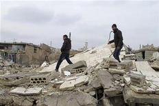 """Imagen de archivo de un grupo residentes revisando edificios derrumbados en Taftanaz, Siria, ene 12 2013. La guerra civil en Siria está desencadenando una """"pasmosa crisis humanitaria"""" en Oriente Medio, con cientos de miles de refugiados que huyen de una ola de violencia que incluye violaciones grupales, dijo el lunes una agencia internacional de ayuda. REUTERS/Abdalghne Karoof"""