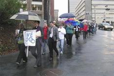 "Same-sex couples and their supporters marched through the streets of downtown Winston-Salem, North Carolina, January 14, 2013 after seeking marriage licenses that they knew they would be denied. They sang ""as long as it takes, love won't be denied"" as they walked in the rain. Holding the ""We Do"" sign at the front is Jasmine Beach-Ferrara, executive director of the Campaign for Southern Equality, which is leading the ""We Do"" push for marriage equality in seven Southern states in January. She also is a minister in the United Church of Christ. REUTERS/Colleen Jenkins"