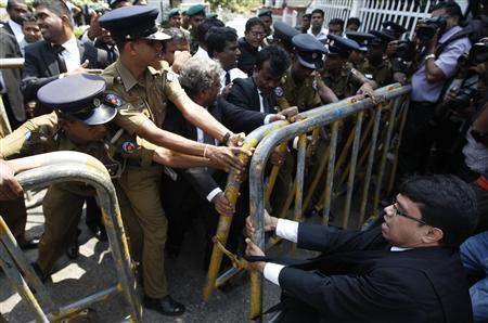 A lawyer attempts to remove a police barrier as police officers try prevent his group from accessing the supreme courts in Colombo January 15, 2013. REUTERS/Dinuka Liyanawatte