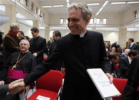 Pope Benedict XVI's personal secretary Georg Ganswein holds a copy of the Pope's book ''The Childhood of Jesus'' during a presentation in Vatican November 20, 2012. REUTERS/Alessandro Bianchi/Files