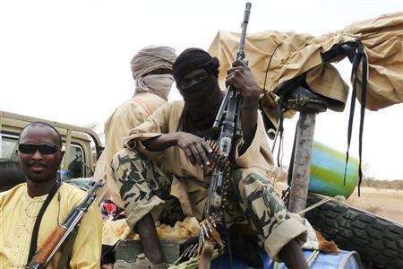 Militiaman from the Ansar Dine Islamic group sit on a vehicle in Gao in northeastern Mali, June 18, 2012. REUTERS/Adama Diarra