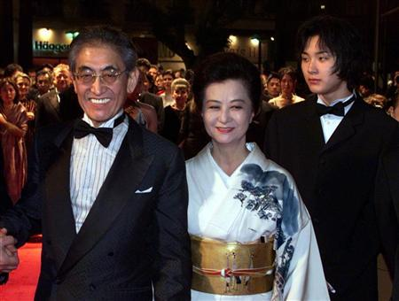 Japanese director Nagisa Oshima (L) arrives with his wife (C) and actor Ryuhei Matsuda (R) as they arrive on the red carpet at the festival palace May 16. Oshima and his cast present their film 'Gohatto' (Taboo) which competes for the Palme d'Or (Golden Palm) at the 53rd Cannes Film Festival May 16. JES/