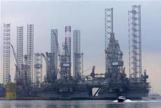 Судно проходит мимо строящихся нефтяных платформ на верфи Keppel FELS Shipyard в Сингапуре 9 сентября 2012 года. Цены на нефть растут на фоне надежд на ускорение роста спроса в США после сообщения о неожиданно значительном повышении розничных продаж в крупнейшем в мире потребителе топлива. REUTERS/Tim Chong