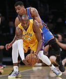 Dwight Howard y Kobe Bryant formaron una combinación letal para mantener el impulso vencedor de los Lakers con una victoria por 104-88 frente a los Bucks de Milwaukee el martes en la que no pudo participar Pau Gasol, quien sigue de baja tras sufrir una conmoción cerebral. En la iamgen, de 11 de enero, Kobe Bryant en una jugada de un partido contra los Thunder de Oklahoma. REUTERS/Lucy Nicholson