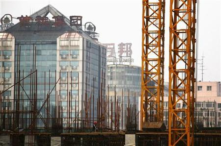 A worker stands amongst scaffolding on a construction site for a new residential building in central Beijing September 21, 2012. REUTERS/David Gray