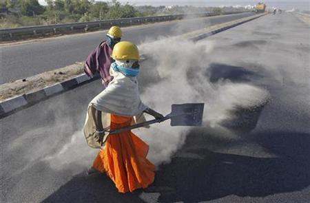 A woman labourer spreads black ash over a newly constructed road at Raipur village, in the western Indian state of Gujarat January 9, 2013. REUTERS/Amit Dave