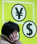 Мужчина разговаривает по телефону возле пункта обмена валют в Токио 1 февраля 2007 года. Доллар возобновил рост к иене после того, как один из японских министров сказал, что его комментарий по поводу курса иены был неверно истолкован. REUTERS/Yuriko Nakao