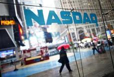 Imagen de archivo de unas personas frente al sitio del mercado Nasdaq en Times Square, EEUU, jun 4 2012. El operador bursátil Nasdaq OMX Group dijo el jueves que combinará sus unidades de software y tecnología, en un esfuerzo por vender más servicios a las empresas que cotizan en sus mercados y generar más ingresos a partir de sus clientes corporativos. REUTERS/Eric Thayer