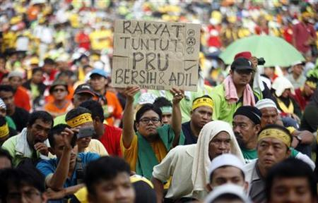 A man holds a placard that reads ''People demand clean and fair elections'' at the Stadium Merdeka during the opposition People's Uprising Rally in Kuala Lumpur January 12, 2013. REUTERS/Samsul Said