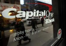 People walk past a Capital One banking center in New York's financial district January 17, 2013. Capital One Financial Corp's fourth-quarter profit missed analysts' expectations as the company set aside more money to cover defaults on its credit cards, sending its shares down 7 percent after the bell. REUTERS/Brendan McDermid