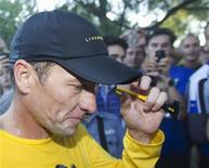 Lance Armstrong walks back to his car after running at Mount Royal park with fans in Montreal August 29, 2012. REUTERS/Christinne Muschi