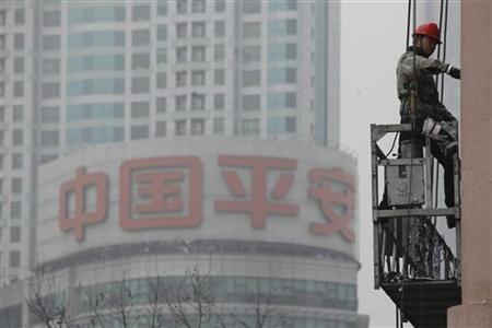 A worker cleans the windows of a building in front of the Ping An Insurance building in Shanghai January 16, 2013. REUTERS/Aly Song (CHINA - Tags: BUSINESS)