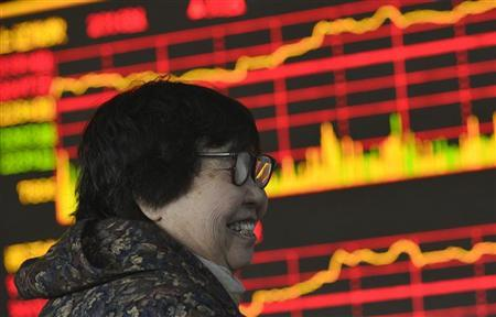 An investor smiles in front of an electronic board showing stock information at a brokerage house in Taiyuan, Shanxi province January 18, 2013. REUTERS/Stringer
