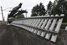 Бригада РЖД меняет железнодорожное полотно на участке Транссибирской магистрали недалеко от станции Тисуль в Кемеровской области 2 июля 2012 года. Горно-металлургическая группа Евраз снизила выплавку стали в 2012 году на 5 процентов, а цены на большую часть продукции упали на фоне проблем мировой экономики, сообщила компания в пятницу. REUTERS/Ilya Naymushin