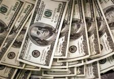 Долларовые банкноты в банке в Вестминстере, штат Колорадо, 3 ноября 2009 года. Миллионеры держатся в стороне от банков и управляющих капиталом, предпочитая вкладывать деньги от продажи акций в недвижимость и новые предприятия, а не в трастовую индустрию, чью репутацию испортил мировой финансовый кризис. REUTERS/Rick Wilking