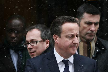 Britain's Prime Minister David Cameron (C) leaves Number 10 Downing Street during snow fall in central London January 18, 2013. REUTERS/Stefan Wermuth