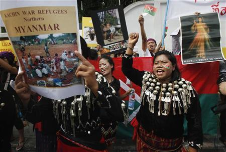 A group of native Kachin living in Thailand hold banners and shout slogans as they protest in front of Myanmar's embassy in Bangkok January 11, 2013. REUTERS/Chaiwat Subprasom