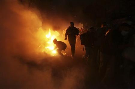 Protesters are seen by firelight as they run from tear gas fired by the military and riot police during clashes along a road which leads to the Interior Ministry, near Tahrir Square in Cairo in this file photo taken November 23, 2011. REUTERS/Amr Abdallah Dalsh