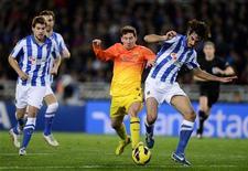 Le Barcelonais Lionel Messi (au centre), à la lutte avec Carlos Martinez, du Real Sociedad, samedi à Saint-Sébastien. Le club catalan, leader de la Liga, a essuyé samedi sur la pelouse de l'équipe basque sa première défaite (3-2) de la saison en championnat d'Espagne après avoir pourtant mené 2-0 à la 25e minute de jeu. /Photo prise le 19 janvier 2013/REUTERS/Vincent West
