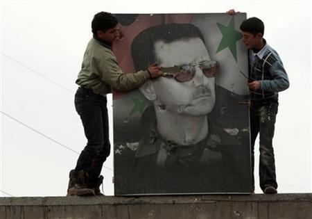 Two boys tear a poster of Syria's President Bashar al-Assad at the army base at Hawa village, north Aleppo December 23, 2012. REUTERS/Ahmed Jadallah/Files