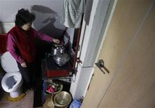 Kong Kyung-soon, 73, who lives alone, does kitchen work in a space that consists of a toilet, bathroom and kitchenette in her tiny rented apartment that has two square meters of living space in Seocho-gu, adjacent to the posh Gangnam suburb, in Seoul January 16, 2013. REUTERS/Lee Jae-Won