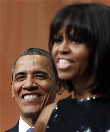 U.S. President Barack Obama smiles as he listens to first lady Michelle Obama at an inaugural reception at the National Building Museum in Washington January 20, 2013. REUTERS/Larry Downing