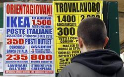 Un ragazzo guarda le offerte di lavoro di un'agenzia a Milano. REUTERS/Alessandro Garofalo
