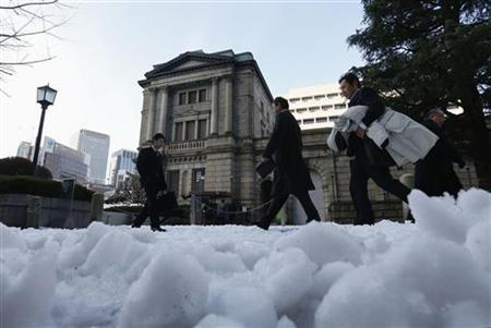 People walk past a street covered with snow in front of the Bank of Japan in Tokyo January 15, 2013. Bank of Japan Governor Masaaki Shirakawa said the central bank will continue with powerful monetary easing as the economy is likely to remain weak for the time being, hardening market expectations that it will expand stimulus again this month. REUTERS/Kim Kyung-Hoon (JAPAN - Tags: BUSINESS ENVIRONMENT)