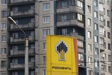 Стояка с логотипом Роснефти на заправке в Санкт-Перебурге, 23 октября 2012 года. Готовящаяся к роли мировой нефтепримы Роснефть замедлила темп прироста запасов нефти в 2012 году, следует из сообщения компании. REUTERS/Alexander Demianchuk