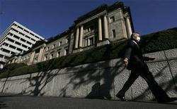 Мужчина проходит мимо Банка Японии в Токио, 20 декабря 2012 года. Банк Японии во вторник повысил инфляционный ориентир до 2 процентов и пообещал неограниченную скупку активов. REUTERS/Kim Kyung-Hoon