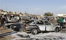 Un grupo de residentes reunidos en la zona de un ataque con bomba en el distrito de Shuala en Bagdad, ene 22 2013. Tres explosiones, entre ellas una causada por un ataque suicida cerca de una base militar, causaron la muerte a 17 personas en Bagdad el martes, en el último episodio de violencia en momentos en que el primer ministro Nuri al-Maliki, un musulmán chií, afronta una creciente presión derivada de una crisis política. REUTERS/Mohammed Ameen