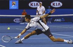 Sérvio Novak Djokovic estica para rebater bola em partida contra o tcheco Tomas Berdych pelas quartas-de-final do Aberto da Austrália, em Melbourne. 22/01/2013 REUTERS/Scott Barbour/Pool