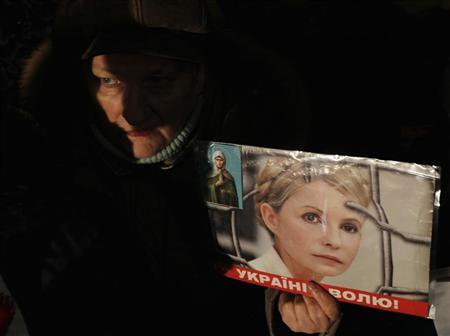 A supporter of opposition parties attends a protest rally and holds up a portrait of jailed former prime minister and opposition leader Yulia Tymoshenko, in front of Ukraine's central electoral commission, in Kiev November 12, 2012. REUTERS/Gleb Garanich
