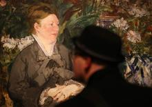 "A visitor looks at ""Madame Manet in the Conservatory"" from 1879 by Edouard Manet in an exhibition entitled ""Manet: Portraying Life"" at the Royal Academy in London January 22, 2013. REUTERS/Suzanne Plunkett"