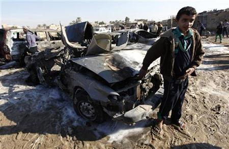 A boy stands near the site of a car bomb attack in the Shuala district of Baghdad,January 22, 2013. REUTERS/Mohammed Ameen