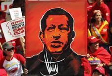 Foto de archivo de un grupo de partidarios del presidente de Venezuela, Hugo Chávez, con un cuadro con su figura en las manos durante un mitin en las afueras del palacio de Gobierno en Caracas, ene 10 2013. El gobierno venezolano dijo el martes que aún no hay una fecha prevista para el regreso al país del presidente Hugo Chávez, a pesar de que aseguró que el mandatario se recupera de una cirugía por un cáncer en Cuba. REUTERS/Carlos Garcia Rawlins