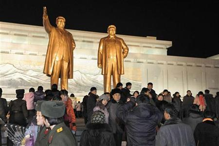 North Koreans visit statues of North Korean founder Kim Il-sung (L) and his son and former leader Kim Jong-il in Pyongyang in this undated photo released by Kyodo January 1, 2013. Mandatory Credit. REUTERS/Kyodo