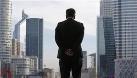 Бизнесмен стоит под Большой аркой Дефанса в деловом центре Парижа 20 ноября 2012 года. Германия, Франция и девять других стран еврозоны получили во вторник разрешение ввести новый налог, в котором Лондон и Люксембург увидели угрозу своим позициям мировых финансовых центров. REUTERS/Christian Hartmann