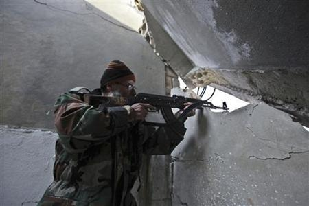 Abou Baker, a 68-years-old fighter of Free Syrian Army, aims his rifle at the front line in Hich village in Idlib January 22, 2013. REUTERS/Gaith Taha