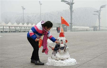 A girl plays with a snowman with a Chinese national flag attached to its hat near the National Stadium, also known as the ''Bird's Nest'', on a hazy day in Beijing January 23, 2013. REUTERS/Stringer