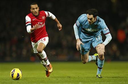 Arsenal's Theo Walcott (L) is challenged by West Ham's Joey O'Brien during their English Premier League soccer match at Emirates Stadium in London January 23, 2013. REUTERS/Eddie Keogh