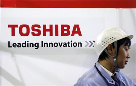 An employee stands next to a logo of Toshiba Corp during a demonstration of the company's new four-legged robot, which the company says is capable of carrying out investigative and recovery work at tsunami-crippled Fukushima Daiichi nuclear power plant, at Toshiba's Yokohama complex in Yokohama, south of Tokyo November 21, 2012. REUTERS/Yuriko Nakao