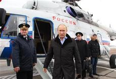 Russian President Vladimir Putin (C) arrives at the town of Krymsk in the Krasnodar region January 11, 2013. REUTERS/Mikhail Klimentyev/RIA Novosti/Pool