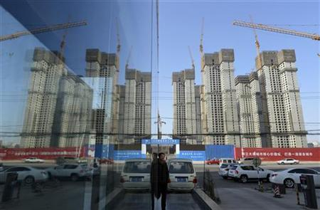 A construction site of a residential compound is reflected on the glass facades of a office building in Taiyuan, Shanxi province, January 15, 2013. REUTERS/Stringer CHINA OUT. NO COMMERCIAL OR EDITORIAL SALES IN CHINA