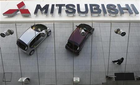 Mitsubishi Motors Corp's vehicles and a passer-by are reflected on an external wall at the company headquarters in Tokyo January 20, 2011. REUTERS/Issei Kato