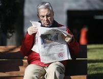 """El diario El País retiró lo que dijo era una """"falsa foto de Hugo Chávez"""" que había publicado en su edición online e impresa el jueves. El presidente venezolano Chávez padece cáncer y está siendo tratado en Cuba, donde fue sometido a una operación quirúrgica en diciembre. No se le ha visto en público desde hace seis semanas. En la imagen, un hombre lee la primera edición del diario El País antes de que fuera retirada, el 24 de enero de 2013. REUTERS/Andrea Comas"""
