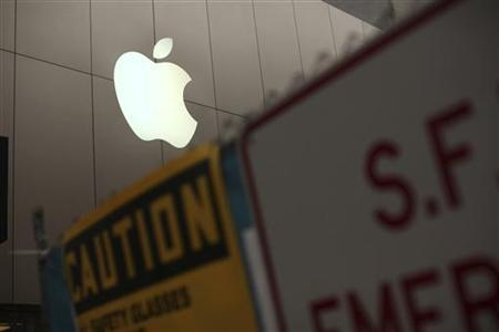 The Apple logo is shown on the front of the company's flagship retail store near signs for the central subway project in San Francisco, California January 23, 2013. REUTERS/Robert Galbraith