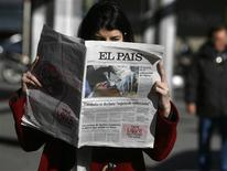 """A woman poses with a copy of the January 24 first edition of Spanish newspaper El Pais in central Madrid January 24, 2013. Spain's influential El Pais newspaper withdrew what it said was """"false photo of Hugo Chavez"""" that it had published in its on-line and print editions on Thursday. REUTERS/Andrea Comas"""