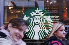 Pedestrians walk past the new Starbucks logo on a store in Times Square in New York March 8, 2011. REUTERS/Lucas Jackson